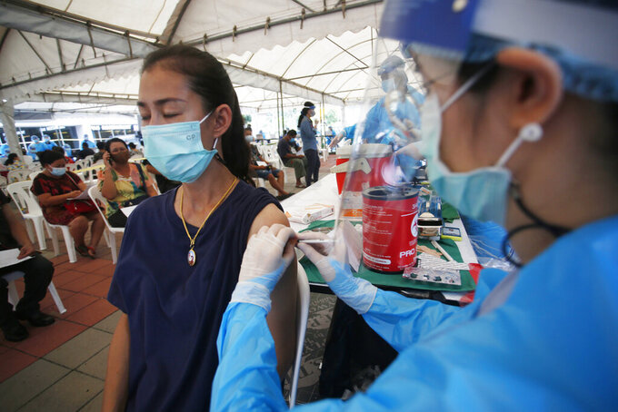 In this Tuesday, May 4, 2021, photo, a health worker administers a dose of the Sinovac COVID-19 vaccine to residents of the Klong Toey area, a neighborhood currently having a spike in coronavirus cases, in Bangkok, Thailand. Health officials rushed to vaccinate thousands of people in Bangkok's biggest slum on Wednesday as a new surge in COVID-19 cases spread through densely populated low-income areas located in the capital's central business district.(AP Photo/Anuthep Cheysakron)