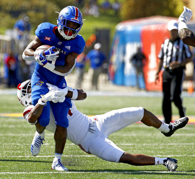 Kansas running back Pooka Williams Jr. (1) is pulled down by Rutgers defensive back Saquan Hampton (9) during the first half of an NCAA college football game Saturday, Sept. 15, 2018, in Lawrence, Kan. (AP Photo/Charlie Riedel)