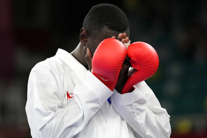 Tareg Hamedi of Saudi Arabia reacts after losing following an injury to Sajad Ganjzadeh of Iran in their men's kumite +75kg gold medal bout for karate at the 2020 Summer Olympics, Saturday, Aug. 7, 2021, in Tokyo, Japan. (AP Photo/Vincent Thian)
