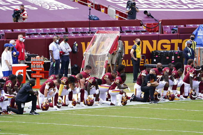 Members of the Washington Football Team kneel on the sidelines before the start of an NFL football game against Philadelphia Eagles, Sunday, Sept. 13, 2020, in Landover, Md. (AP Photo/Susan Walsh)