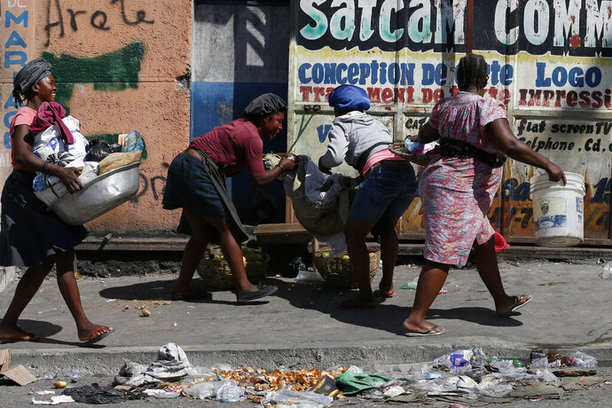 Vendors scramble to pack up their goods and get inside, as protesters calling for President Jovenel Moïse march up a road in downtown Port-au-Prince, Haiti, Monday, Oct. 21, 2019. Anger over corruption, inflation and scarcity of basic goods including fuel has led to large demonstrations that began more than a month ago and have shuttered many businesses and schools.(AP Photo/Rebecca Blackwell)