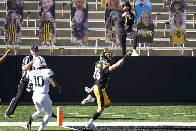 Iowa's Charlie Jones (16) scores a touchdown on a 54-yard punt return ahead of Michigan State's Michael Dowell (10) during the first half of an NCAA college football game, Saturday, Nov. 7, 2020, in Iowa City, Iowa. (AP Photo/Charlie Neibergall)