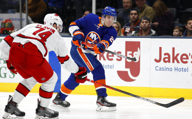 FILE - In this March 7, 2020, file photo, then-New York Islanders defenseman Devon Toews (25) shoots the puck as Carolina Hurricanes defenseman Jaccob Slavin (74) tries to defend during an NHL hockey game, in Uniondale, N.Y. The Colorado Avalanche have agreed to a four-year deal with newly acquired defenseman Devon Toews. The contract for Toews runs through the 2023-24 season, the team announced Tuesday, Oct. 27, 2020. (AP Photo/Jim McIsaac, File)