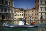 Financial Police patrols Canal Grande, in Venice, Monday, April 6, 2020. The government is demanding Italians stay home and not take the leveling off of new coronavirus infections as a sign the emergency is over, following evidence that more and more Italians are relaxing restrictions the west's first and most extreme nationwide lockdown and production shutdown. The new coronavirus causes mild or moderate symptoms for most people, but for some, especially older adults and people with existing health problems, it can cause more severe illness or death. (AP Photo/Andrew Medichini)