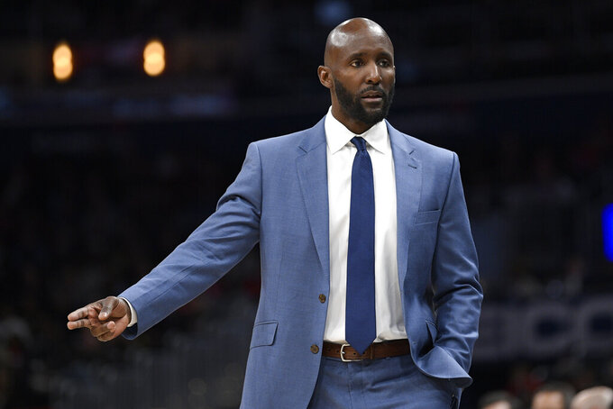 """FILE - In this March 6, 2020, file photo, Atlanta Hawks coach Lloyd Pierce gestures during the first half of the team's NBA basketball game against the Washington Wizards in Washington. The teams that didn't qualify for the restart of the NBA season at Walt Disney World could begin voluntary workouts Wednesday, Sept. 23, to start preparing for their next game — whenever that is. """"I've never seen a layup drill with such intensity,"""" Pierce said. """"We did a full-court layup drill and the guys were clapping and cheering. You know they haven't practiced in a long time if they're excited about layup drills."""" (AP Photo/Nick Wass, File)"""