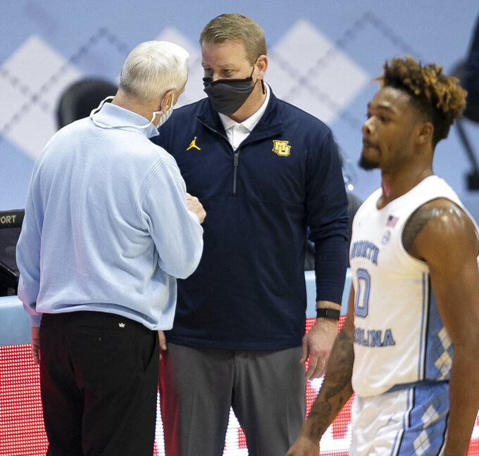 North Carolina coach Roy Williams congratulates Marquette coach Steve Wojciechowski after Marquette's win in an NCAA college basketball game Wednesday, Feb. 24, 2021, in Chapel Hill, N.C. (Robert Willett/The News & Observer via AP)