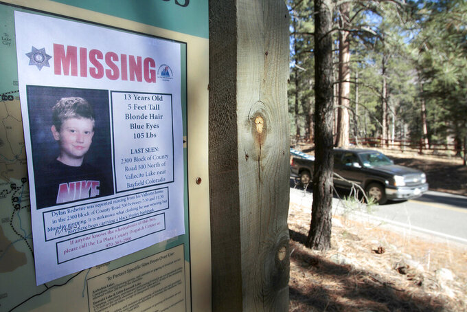 FILE - In this Nov. 26, 2012, file photo, a missing poster of 13-year-old Dylan Redwine hangs on a trail head sign next to Vallecito Reservoir in Vallecito, Colo. Opening statements are expected sometime Monday, June 21, 2021, in the delayed trial of a man accused of killing his 13-year-old son in southwest Colorado nearly a decade ago. Dylan Redwine disappeared during a court ordered Thanksgiving visit in 2012 and his remains were later found. (Shaun Stanley/The Durango Herald via AP, File)