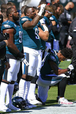 FILE - In this Sept. 20, 2020, file photo, Philadelphia Eagles defensive tackle Fletcher Cox (91) stands for during the national anthem as defensive tackle Malik Jackson (97) keeps a fist raised and free safety Rodney McLeod (23) kneels before the team's NFL football game against the Los Angeles Rams in Philadelphia. While the NFL fights for racial equality, current and former players want team owners to take more specific actions. Jackson has a suggestion that has been voiced by many people from players to activists. He wants owners to hire more Black coaches, general managers and high-ranking executives. (AP Photo/Corey Perrine, File)