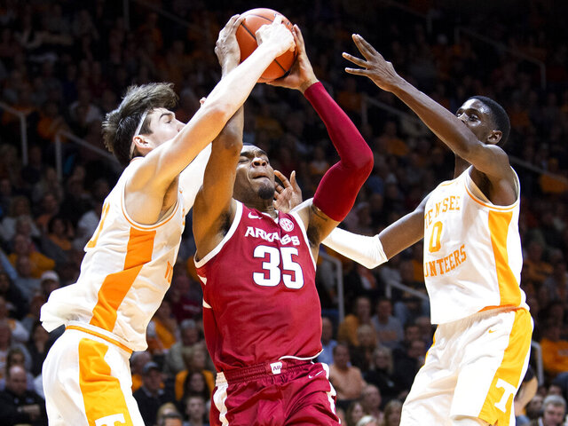 Arkansas forward Reggie Chaney (35) is defended by Tennessee forward John Fulkerson (10) and Tennessee guard Davonte Gaines (0) during an NCAA college basketball game, Tuesday, Feb. 11, 2020 in Knoxville, Tenn. (Brianna Paciorka/Knoxville News Sentinel via AP)