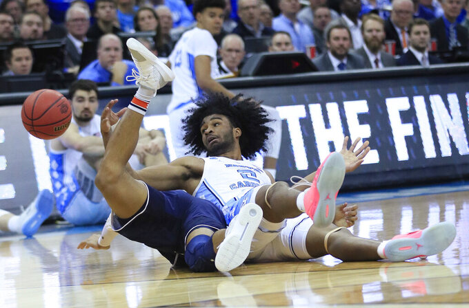 North Carolina's Coby White (2) and Auburn's Bryce Brown dive after a loose ball during the second half of a men's NCAA tournament college basketball Midwest Regional semifinal game Friday, March 29, 2019, in Kansas City, Mo. (AP Photo/Orlin Wagner)