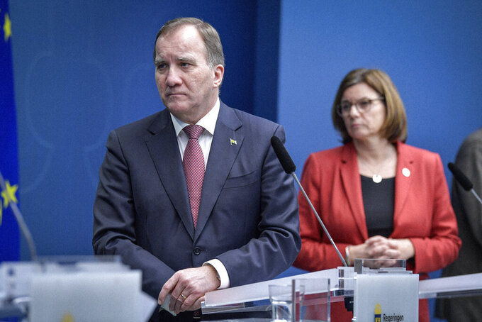 Sweden's Prime Minister Stefan Lofven and Deputy Prime Minister Isabella Lovin hold a coronavirus news conference, in Stockholm, Friday, Dec. 18,2020. The Swedish government is tightening nationwide coronavirus restrictions by lowering the number of people who can gather in a restaurant and making face masks mandatory on public transportation. Sweden has stood out among European nations for its comparatively hands-off response to the pandemic. (Jessica Gow/TT News Agency via AP)