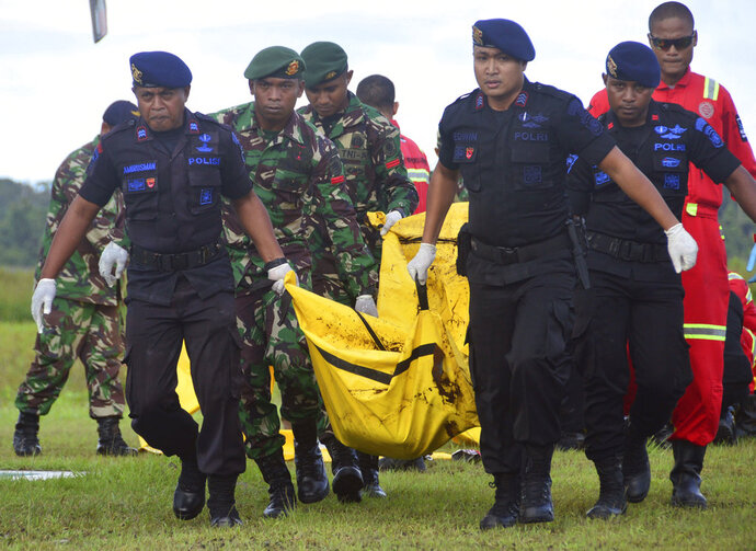 Indonesian soldiers and police officers carry a body bag containing the body of a victim of separatist attack in Nduga district upon its arrival at Moses Kilangin Airport in Timika, Papua province, Indonesia, Friday, Dec. 7, 2018. Army helicopters on Friday transported bodies of the victims who were killed in one of the bloodiest separatist attacks in Indonesia's restive Papua province. (AP Photo/Mujiono)