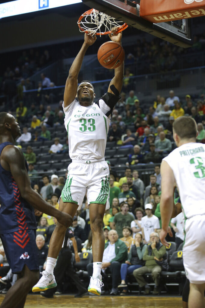 Oregon's Francis Okoro, center, dunks between Fresno State's Nate Grimes, left, and Oregon's Payton Pritchard during the first half of an NCAA college basketball game in Eugene, Ore., Tuesday, Nov. 5, 2019. (AP Photo/Chris Pietsch)