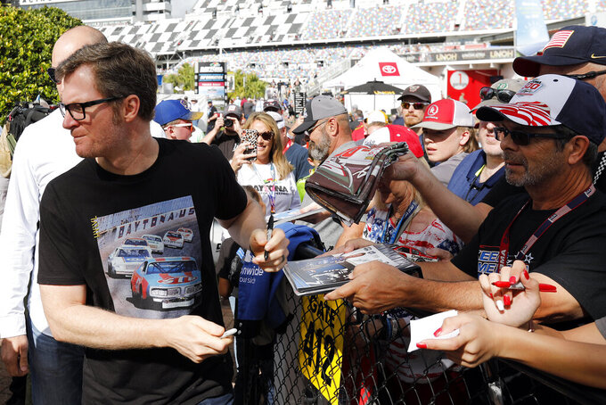 Dale Earnhardt Jr., team owner and TV analyst signs autographs outside the media center before the NASCAR Daytona 500 auto race at Daytona International Speedway, Sunday, Feb. 16, 2020, in Daytona Beach, Fla. (AP Photo/Terry Renna)