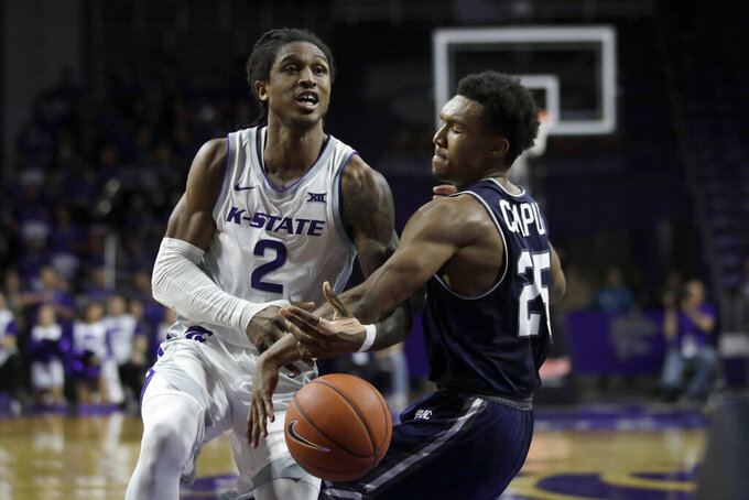 Monmouth guard Samuel Chaput (25) knocks the ball away from Kansas State guard Cartier Diarra (2) during the second half of an NCAA college basketball game in Manhattan, Kan., Wednesday, Nov. 13, 2019. (AP Photo/Orlin Wagner)