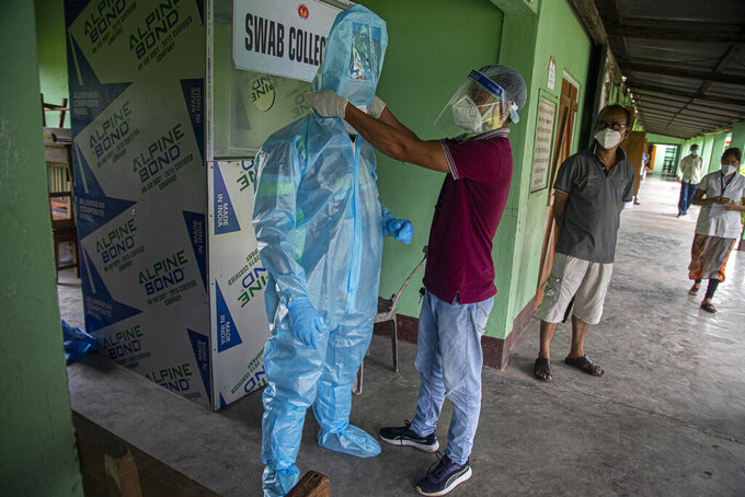 An Indian health worker helps another to wear personnel protection equipment kit before he collects nasal swab samples at a COVID-19 testing center in Gauhati, Assam state, India, Sunday, July 12, 2020. India is the world's third worst-affected country by the coronavirus. (AP Photo/Anupam Nath)