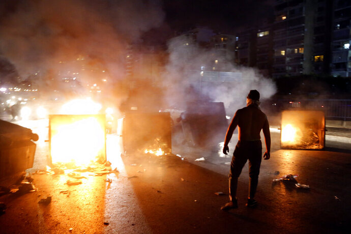 A supporter of Lebanese Prime Minister Saad Hariri burns garbage containers to block  a main road, in Beirut, Lebanon, Tuesday, Oct. 29, 2019. Hariri resigned Tuesday, bowing to one of the central demands of anti-government demonstrators shortly after baton-wielding Hezbollah supporters rampaged through the main protest camp in Beirut, torching tents, smashing plastic chairs and chasing away protesters. (AP Photo/Bilal Hussein)