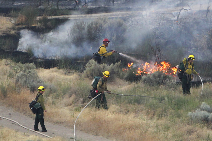 FILE - In this June 30, 2016 file photo firefighters respond to a wildfire near the Morningside Heights neighborhood near Table Rock in east Boise, Idaho. With a potential ferocious wildfire season ready to ignite across the western U.S., the push is on to persuade state and federal wildland firefighters to get vaccinated against COVID-19. Republican Idaho Gov. Brad Little said Tuesday, May 18, 2021, that lives could be lost if frontline firefighters get sidelined with the illness. (Joe Jaszewski/Idaho Statesman via AP, File)