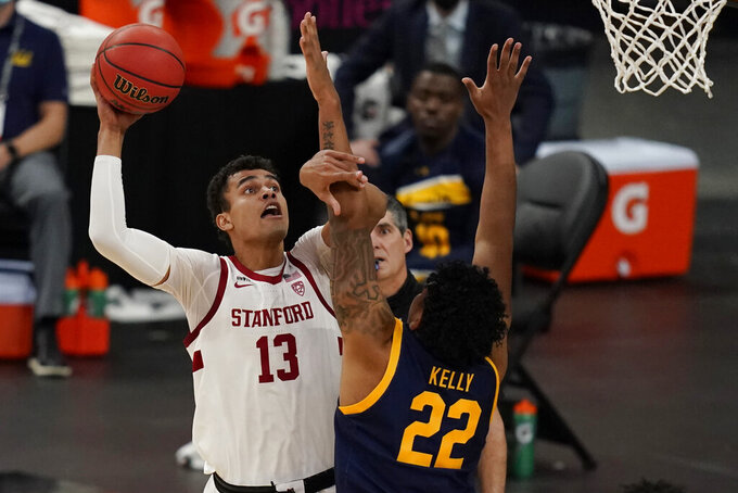 Stanford's Oscar da Silva (13) shoots over California's Andre Kelly (22) during the first half of an NCAA college basketball game in the first round of the Pac-12 men's tournament Wednesday, March 10, 2021, in Las Vegas. (AP Photo/John Locher)