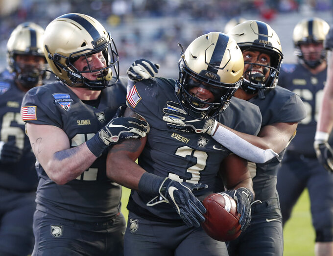 Army running back Jordan Asberry (3) celebrates his touchdown with wide receiver Glen Coates, right, and running back Connor Slomka, left, during the second half of Armed Forces Bowl NCAA college football game against Houston on Saturday, Dec. 22, 2018, in Fort Worth, Texas. Army won 70-14. (AP Photo/Jim Cowsert)