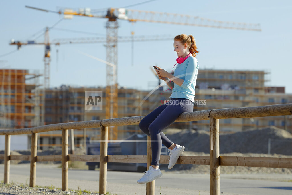 Woman using mobile phone while sitting on railing