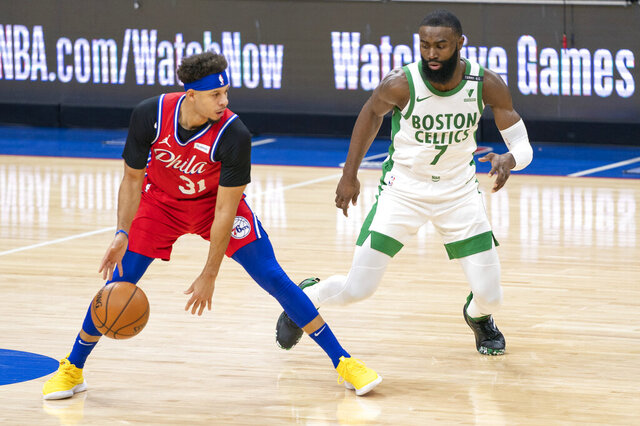 Philadelphia 76ers' Seth Curry, left, looks to make his move against Boston Celtics' Jaylen Brown, right, during the first half of an NBA basketball game, Friday, Jan. 22, 2021, in Philadelphia. (AP Photo/Chris Szagola)