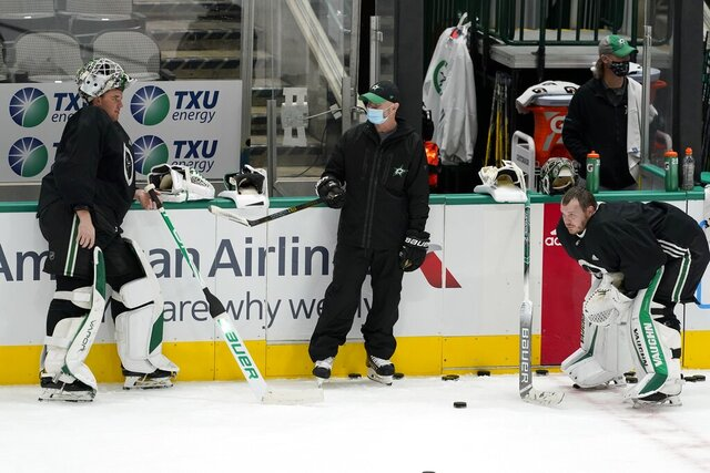 Dallas Stars goalies Jake Oettinger, left, and Anton Khudobin, right, listen to goaltending coach Jeff Reese, center, during NHL hockey practice in Dallas, Thursday, Jan. 21, 2021. (AP Photo/Tony Gutierrez)