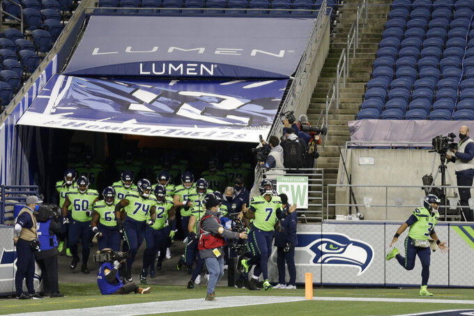 Seattle Seahawks players run out of the tunnel under a new sign that reads Lumen Field, the new name of the Seahawks' stadium, before an NFL football game against the Arizona Cardinals, Thursday, Nov. 19, 2020, in Seattle. The field name was changed because CenturyLink, the current name-rights holder, has rebranded to be named Lumen Technologies. (AP Photo/Lindsey Wasson)