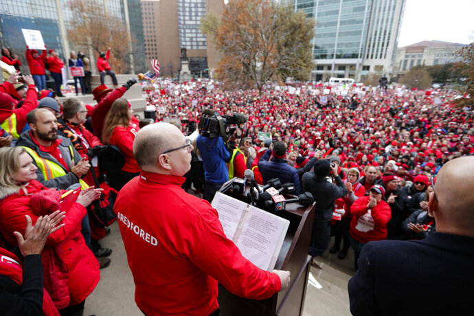 Keith Gambill, president of the Indiana State Teachers Association, of Evansville, Ind., speaks to the thousands of Indiana teachers wearing red as they surrounded the Statehouse in Indianapolis, Tuesday, Nov. 19, 2019 for a rally calling for further increasing teacher pay in the biggest such protest in the state amid a wave of educator activism across the country. Teacher unions says about half of Indiana's nearly 300 school districts are closed while their teachers attend Tuesday's rally while legislators gather for 2020 session organization meetings.(AP Photo/Michael Conroy)