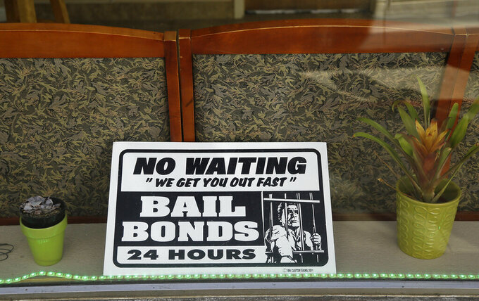 FILE - In this Dec. 23, 2015, file photo, a sign is seen in the window of a bail bonds office across from the Hall of Justice in San Francisco. The California Supreme Court ruled Thursday, March 25, 2021, that judges must consider suspects' ability to pay when they set bail, essentially requiring that indigent defendants be freed unless they are deemed too dangerous to be released awaiting trial. (AP Photo/Eric Risberg, File)