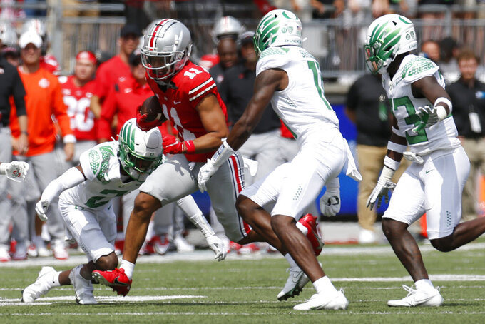 Ohio State receiver Jaxon Smith-Njigba, center, cuts up field against Oregon defenders Mykael Wright, left, and Trikweze Bridges during the first half of an NCAA college football game Saturday, Sept. 11, 2021, in Columbus, Ohio. Oregon beat Ohio State 35-28. (AP Photo/Jay LaPrete)