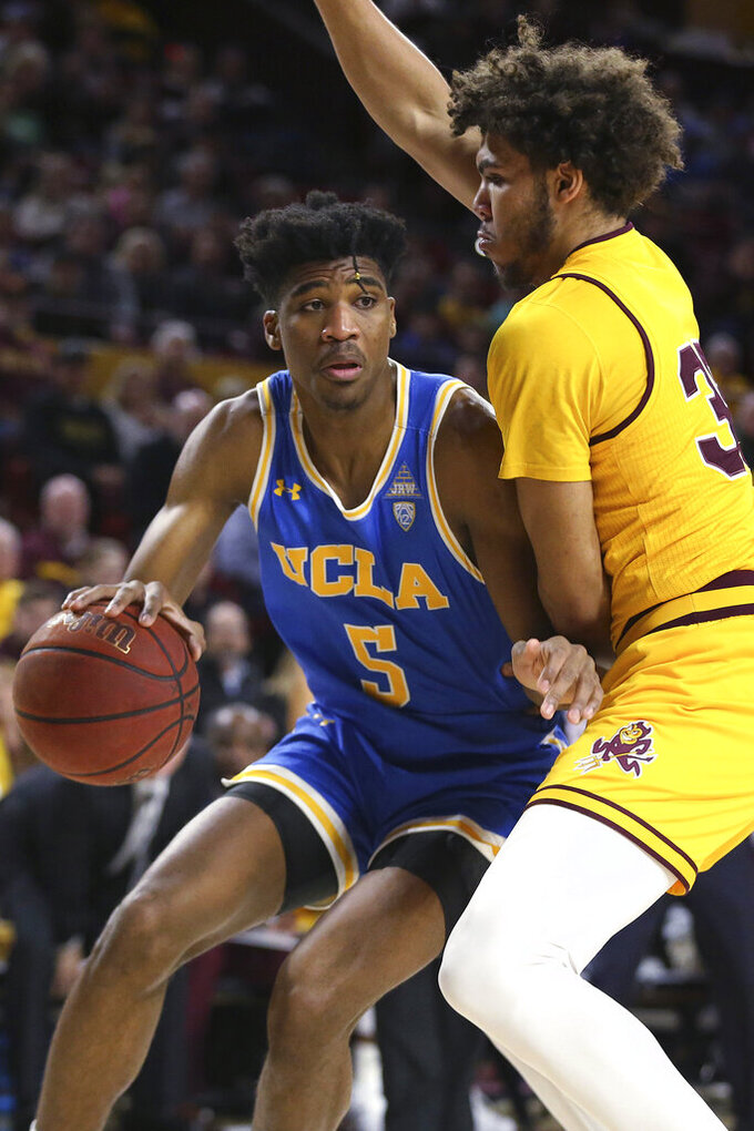 UCLA's Chris Smith (5) looks for an opening while being covered by Arizona State's Tahshon Cherry (35) during the first half of an NCAA college basketball game Thursday, Feb. 6, 2020, in Tempe, Ariz. (AP Photo/Darryl Webb)