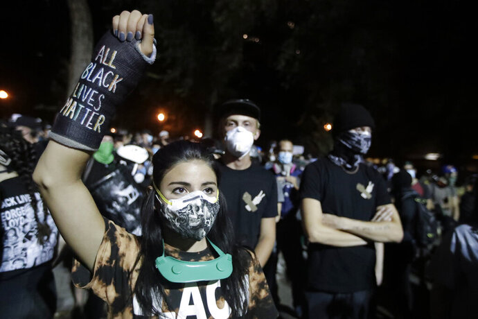 A demonstrator raises her fist while listening to a speech during a Black Lives Matter protest at the Mark O. Hatfield United States Courthouse Thursday, July 30, 2020, in Portland, Ore. After days of clashes with federal police, the crowd outside of the federal courthouse remained peaceful Thursday night. (AP Photo/Marcio Jose Sanchez)