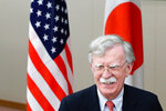 U.S. National Security Advisor John Bolton walks past U.S. and Japanese flags prior to a meeting with Japanese Foreign Minister Taro Kono in Tokyo Monday, July 22, 2019. (AP Photo/Eugene Hoshiko)