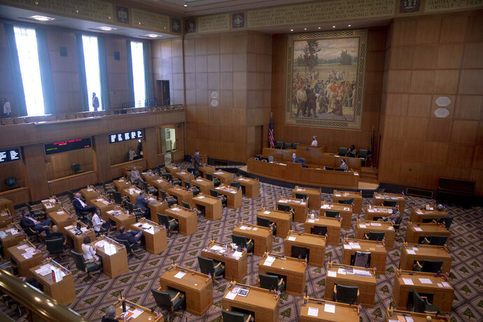 The House works to adopts rules during a special session of the state Legislature at the Capitol in Salem, Ore., Monday, Aug. 10, 2020. Oregon lawmakers discussed unemployment benefits and police reform bills as they returned to the Capitol for a special session that was largely supposed to be focused on the state's $1 billion budget hole due to the COVID-19 pandemic. (Brian Hayes/Statesman Journal via AP)