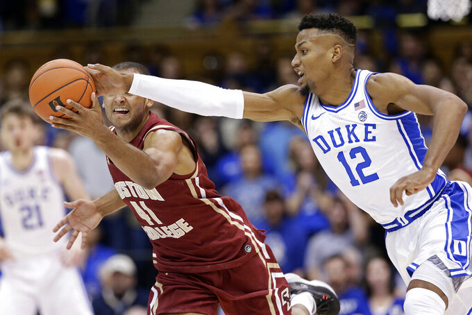 Duke forward Javin DeLaurier (12) amd Boston College forward Steffon Mitchell (41) chase the ball during the first half of an NCAA basketball game in Durham, N.C., Tuesday, Dec. 31, 2019. (AP Photo/Gerry Broome)