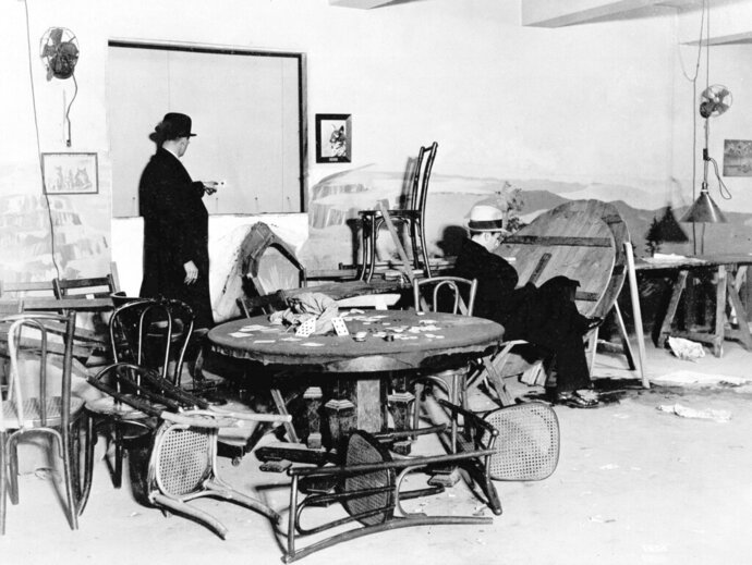 FILE - In this Dec. 31, 1931, file photo the wrecked speakeasy in the Hotel Victoria in mid-Manhattan, where Louis Levine, alias Louis Taylor, a small-time gambler, was killed by one of three gunmen earlier in the day in New York. A bystander points to a bullet hole in the wall, while another is seated in the chair where Levine, known as