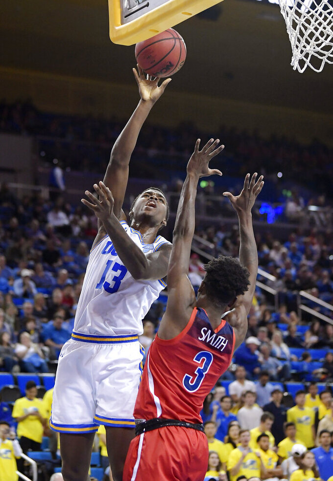 UCLA guard Kris Wilkes, left, shoots as Arizona guard Dylan Smith defends during the second half of an NCAA college basketball game Saturday, Jan. 26, 2019, in Los Angeles. UCLA won 90-69. (AP Photo/Mark J. Terrill)