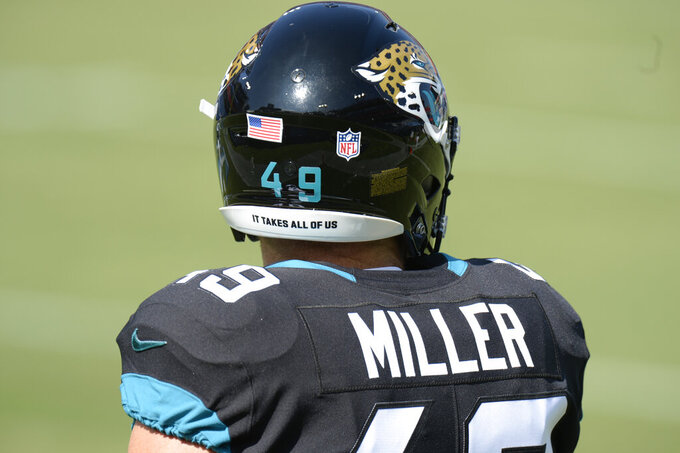 Jacksonville Jaguars running back Bruce Miller (49) wears a social justice logo on his helmet as he warms up before an NFL football game against the Tennessee Titans Sunday, Sept. 20, 2020, in Nashville, Tenn. (AP Photo/Mark Zaleski)