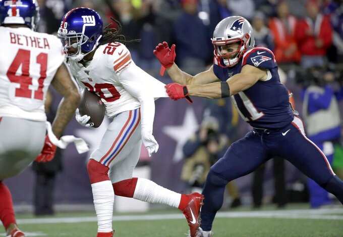 New York Giants cornerback Janoris Jenkins, left, runs with the ball after intercepting a pass intended for New England Patriots wide receiver Julian Edelman, right, in the first half of an NFL football game, Thursday, Oct. 10, 2019, in Foxborough, Mass. (AP Photo/Elise Amendola)