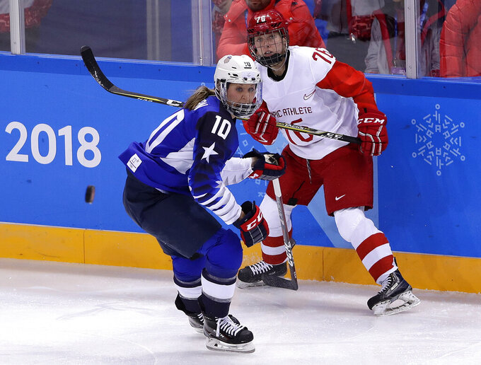 FILE - In this Feb. 13, 2018, file photo, Meghan Duggan (10), of the United States, and Yekaterina Nikolayeva (76), of Russia, chase the puck during the first period of the preliminary round of the women's hockey game at the Winter Olympics in Gangneung, South Korea. U.S. women's hockey captain Duggan announced her retirement Tuesday, Oct. 13, 2020, after a career in which she won the 2018 Olympic gold medal and seven world championship golds. (AP Photo/Frank Franklin II, File)