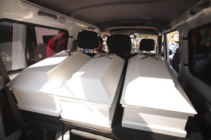Coffins holding the remains of three of six family members who were killed in a 1982 massacre are transported by the forensic office to be handed over to the victims' family in San Salvador, El Salvador, Thursday, Jan. 23, 2020. The remains of six adults and children from one family were handed over to surviving relatives on Thursday, 38 years after the El Calabozo massacre in which government soldiers are accused of killing more than 200 people. (AP Photo/Salvador Melendez)