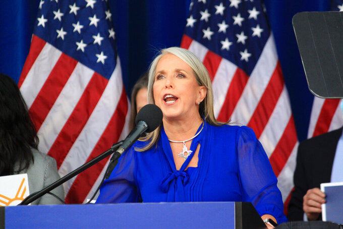 New Mexico Gov. Michelle Lujan Grisham declares her intention to seek reelection during a campaign rally in Albuquerque, New Mexico, on Thursday, June 3, 2021, as protesters chanted loudly beyond the walls of the outdoor venue. (AP Photo/Susan Montoya Bryan)