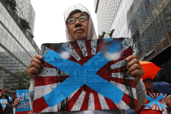 FIEL - In this Aug. 15, 2019, file photo, South Korean protesters hold Japanese rising sun flags during a rally to mark the South Korean Liberation Day from Japanese colonial rule, in downtown Seoul, South Korea. South Korea has formally asked the International Olympic Committee to ban the Japanese