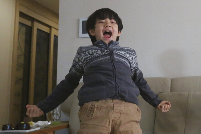 Parasite actor Jeong Hyeonjun celebrates as he watches a TV live broadcasting of South Korean director Bong Joon Ho receiving the award for best original screenplay for