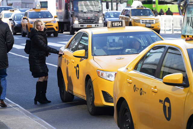 FILE- In this Jan. 29, 2020, file photo, a passenger gets into a taxi in New York. New York Attorney General Letitia James announced Thursday, Feb. 20, 2020, plans to sue New York City for $810 million for inflating the price of taxi medallions, which were marketed as a sure-fire investment before ride-hailing apps upended the taxi industry.(AP Photo/Mark Lennihan, File)