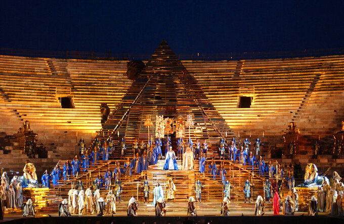 "FILE - In this  June 21, 2002 file photo, a huge pyramid dominates the stage of the opening performance of Giuseppe Verdi's Aida in the Verona Arena, northern Italy. Riccardo Muti will open the season on June 19 and 22, conducting a concert version of ""Aida"" to mark the 150th anniversary of the Verdi title whose pageantry has made it a festival mainstay. (AP Photo/Claudio Martinelli)"