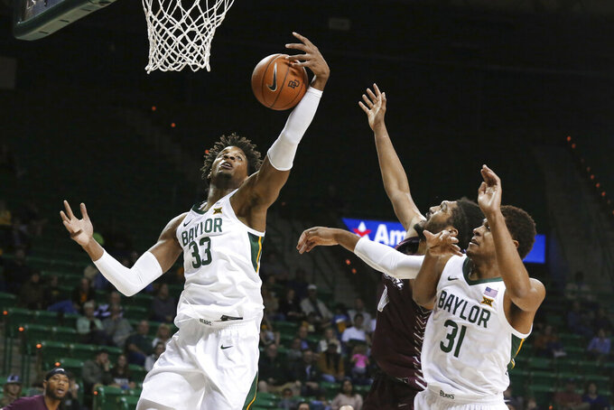 Baylor forward Freddie Gillespie, left, grabs a rebound over Maryland-Eastern Shore forward AJ Cheeseman and teammate MaCio Teague, right, in the first half of an NCAA college basketball game, Tuesday, Dec. 3, 2019, in Waco, Texas. Baylor won 78-46. (AP Photo/Rod Aydelotte)