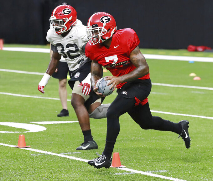 Georgia tailback D' Andre Swift, right, runs a drill during team practice for the Sugar Bowl at Mercedes-Benz Superdome on Saturday, December 28, 2019, in New Orleans. (Curtis Compton/Atlanta Journal-Constitution via AP)