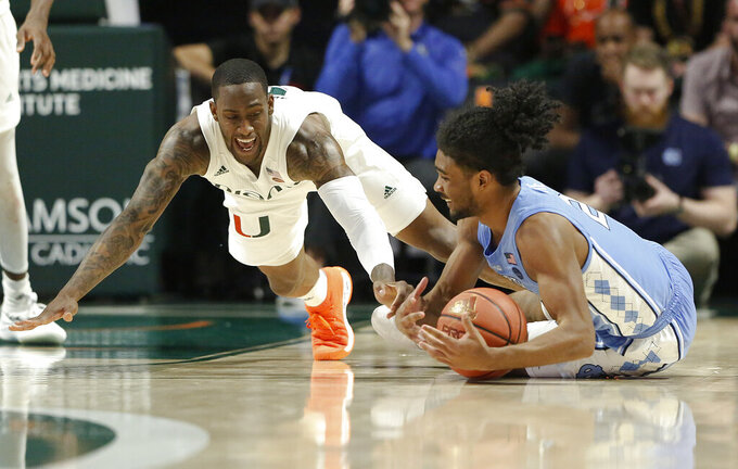 Miami guard Zach Johnson, left, dives for the ball against North Carolina guard Coby White during the second half of an NCAA college basketball game on Saturday, Jan. 19, 2019, in Coral Gables, Fla. (AP Photo/Brynn Anderson)